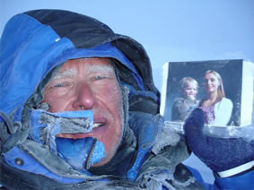 Alan Hinkes holding picture of family in a very cold enviroment